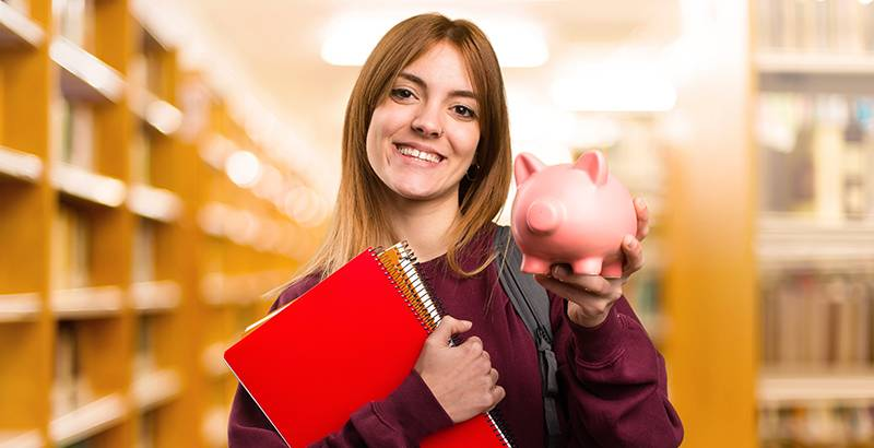 Girl holding book and piggy bank